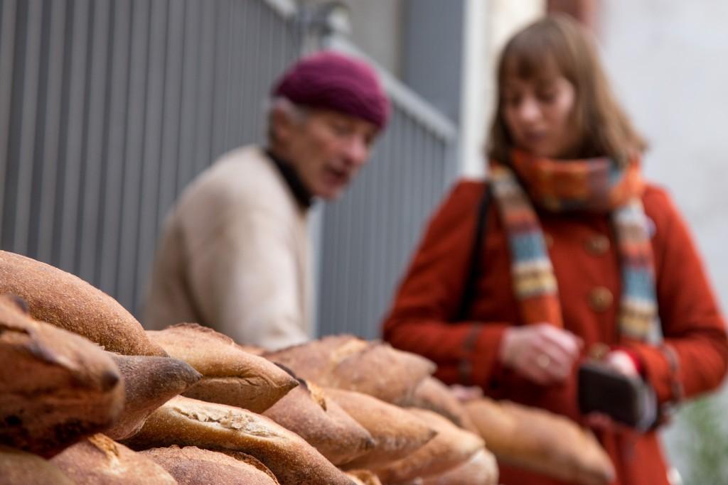 Samedi 9 janvier 2016., Jean-François Vienne, boulanger et propriétaire du Four Banal, est attentionné envers ses clients au marché bio du 104, Paris 19ème.